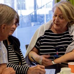 Kaksi työpajan osallistujaa keskustelemassa pöydän äärellä.