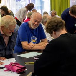 Työpajaan osallistujien joukkoa, neljä senioria ja keskustelun vetäjä pöydän ääressä.