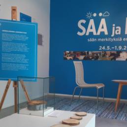 Kuva Sää ja mää -näyttelyn sisätiloista. Kuvassa mm. puukiekkoja pöydällä ja näyttelytekstejä.