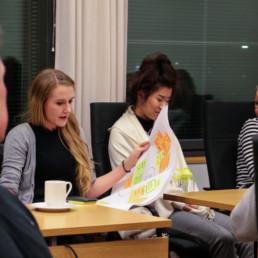Pöydän äärellä nuoria ja aikuisia, arkkitehti Anni Laurila pitää työpajapaperia käsissään.