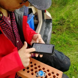 Henkilöllä sylissään tiiliskivi, jossa kiinni pyöreä mittauslaite. Hän syöttää puhelimeen mittarin sijaintitietoja.