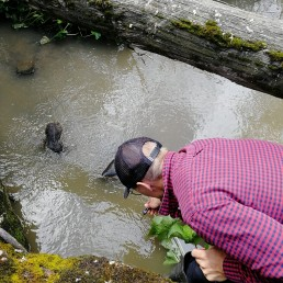 Henkilö kumartuneena puron rannalla lämpömittari kädessään.