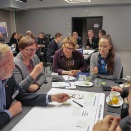 Ihmisiä pöydän äärellä työpajassa, keskellä yhteinen paperi, johon kirjoitetaan.
