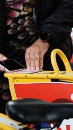 Seniori ottaa kaupunkipyörää käyttöön näyttämällä korttia pyörän laitteelle.