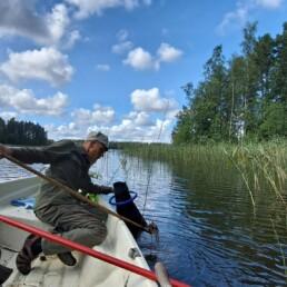 Kuvassa henkilö veneessä järvellä aurinkoisena päivänä mukanaan tutkimisvälineitä.