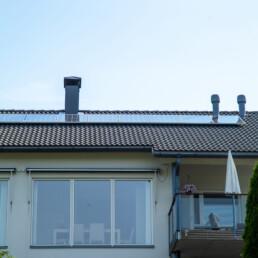 Edestä päin kuvattu kerrostalo, jossa parvekkeita ja katolla aurinkopaneelit.