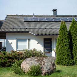 Valkoinen pientalo, jonka katolla aurinkopaneelit, edessä pihaistutuksia.