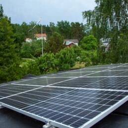 Kuvassa näkymä pientalon katolta. Etualalla aurinkopaneelit, taustalla vehreää maisemaa.
