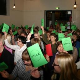 Yleisöä nostamassa vihreitä ja punaisia äänestyslippuja.