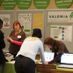 Valonian neuvontapiste, jossa julisteita, infokylttejä ja opiskelijoita keskustelemassa.